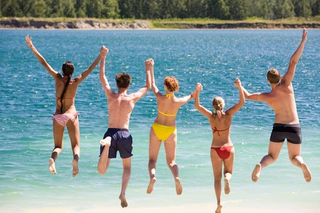 dynamic activity: Rear view of friends holding by hands and jumping into water Stock Photo