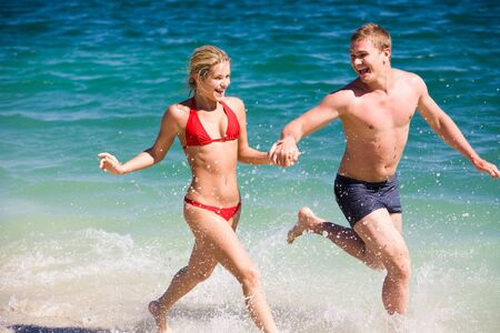 guy on beach: Image of happy teenage couple running by the seashore on summer day Stock Photo