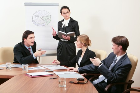 Image of successful people sitting around table and sharing experience with elegant female listening to them attentively photo