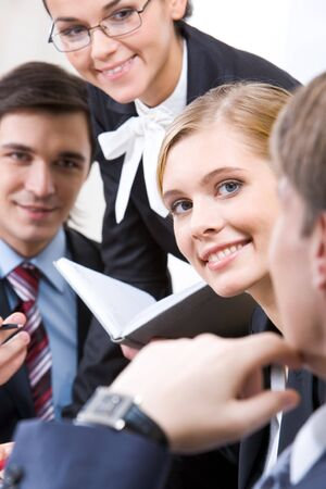 Happy face of pretty employee among her interacting colleagues Stock Photo - 4443447