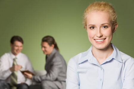 Portrait of blond girl looking at camera with two interacting businessmen at background photo
