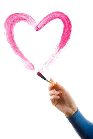 Image of female hand with painting brush drawing shape of heart on white background photo