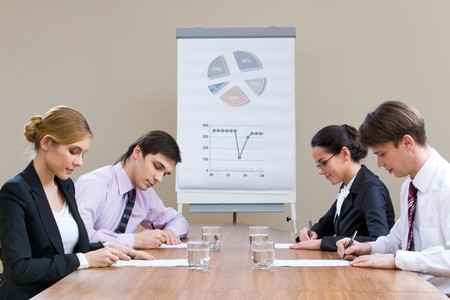 briefing: Two rows of businesspeople having written work at briefing Stock Photo