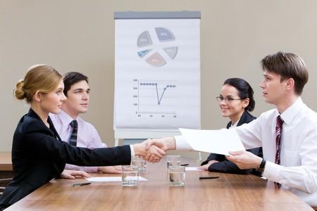 businesspartners: Foto de businesspartners agitando las manos despu�s de hacer un acuerdo con sus compa�eros de trabajo buscando en ellos Foto de archivo