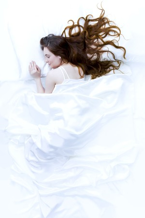 Above view of young beautiful woman sleeping in bed covered with white silky sheet Stock Photo - 4443495