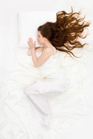 silky hair: Above view of sleeping woman under white satin sheet Stock Photo