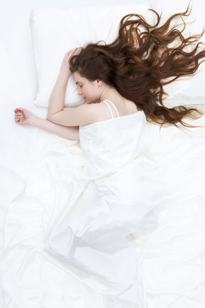 woman sleep: Image of peaceful girl lying on linen bed under satin cloth and dreaming Stock Photo