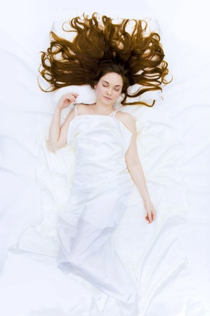 Above view of resting female under linen sheet with her long hair spread on pillow Stock Photo - 4443546
