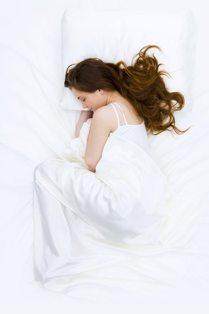 Serene woman covered with silk cloth lying in bed and having a nap photo