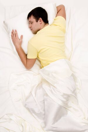 arms above head: Shot from above of tranquil male sleeping in comfortable bed at night
