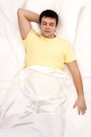 arms above head: Above view of man with one hand under his head sleeping in cosy bed