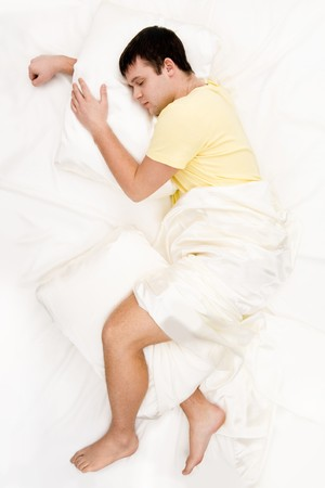 Above view of peaceful man having pleasant sleep on his comfortable bed