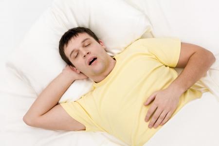 gente durmiendo: Vista desde arriba del hombre cansado, mientras que el ronquido profundo sue�o en la cama Foto de archivo