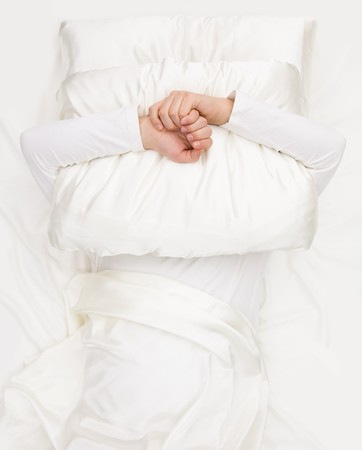 shutting: Image of male hands embracing pillow and shutting his face with it Stock Photo