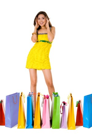 spree: Portrait of astonished female in yellow glamorous dress with colorful paperbags in front