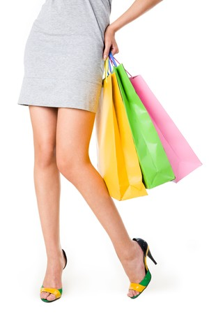 spree: Close-up of beautiful female legs and three bags in her hand touching hip