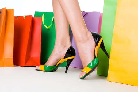 Close-up of female legs wearing stylish shoes surrounded by colorful paperbags Stock Photo - 4467455