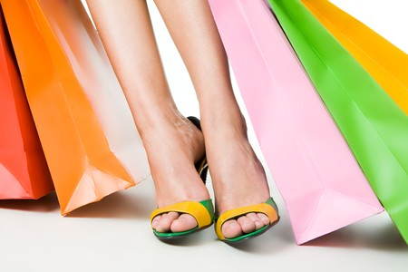 Close-up of feminine legs in shoes with paperbags near by over white background Stock Photo - 4467458