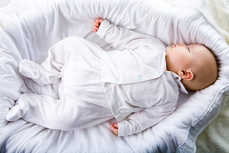 Above view of fragile baby having a nod in comfortable cradle at home photo