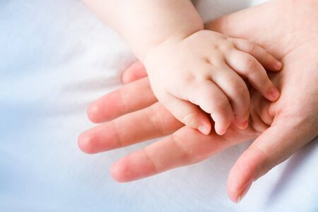 gentleness: Image of mom�s palm with newborn baby hand on its surface Stock Photo