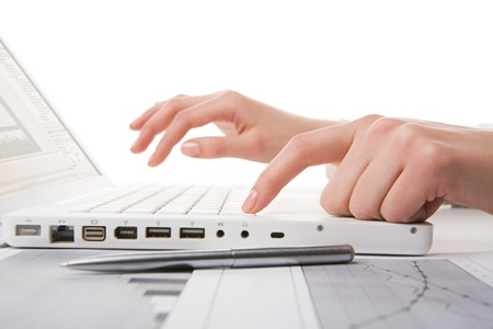 Human hands over laptop keypad typing on it with silver pen near by photo