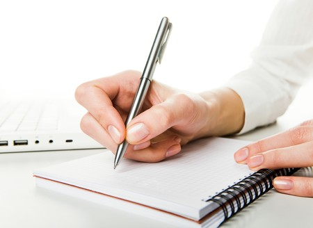 page down: Close-up of human hand before writing down business plan on page of notepad