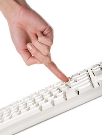 Image of human forefinger pushing button of computer keyboard photo