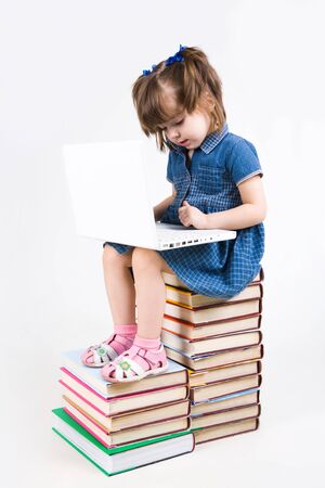 Photo of schoolgirl sitting on books and learning how to use laptop photo
