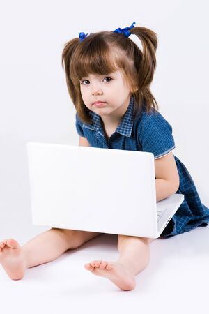 little girl barefoot: Curious girl sitting with laptop on her knees and looking at camera Stock Photo