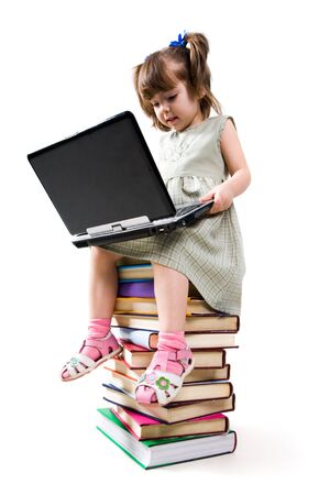 Photo of clever child with laptop on her knees looking at its keypad photo