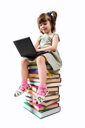 Clever elementary class child sitting on pile of textbooks and typing on laptop photo