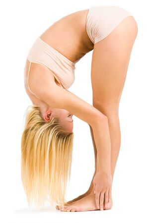 Young fit girl standing in inclined position touching floor by her fingers and hair photo