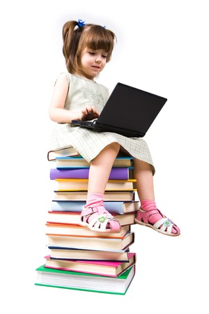Portrait of clever girl sitting on books with laptop in front and typing photo