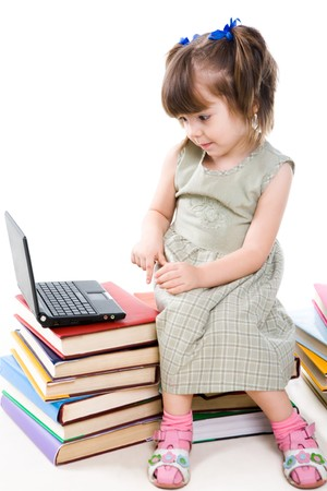 Image of curious preschooler sitting on books and looking at laptop display photo