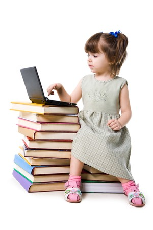 Smart little girl sitting before laptop with her forefinger over button of keypad photo