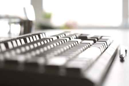 near side: Side view of personal computer keyboard with pen near by Stock Photo