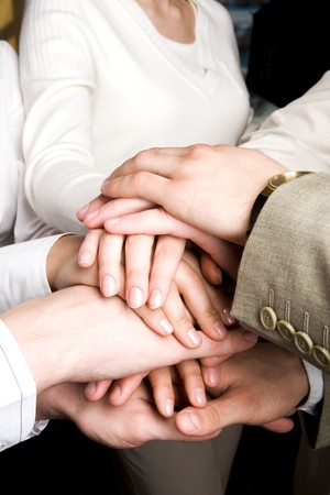 partnership security: Close-up of pile of partners� hands over each other