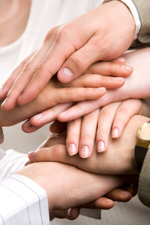 Symbol of companionship between business people shown by pile of their hands