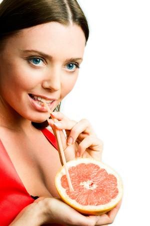 Photo of beautiful girl drinking fresh natural juice from orange photo