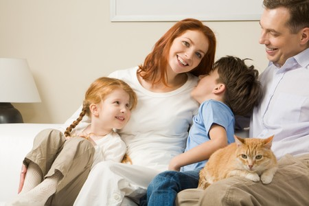 Portrait of happy parents and their children sitting on the sofa with red cat on man�s knees photo