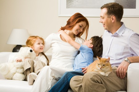 mom and son: Photo of cute boy embracing his pretty mother surrounded by playful daughter and their father Stock Photo