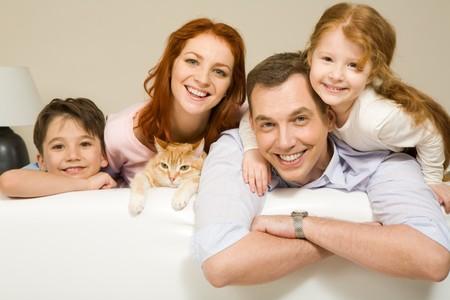 Retrato de los hermanos y sus padres con lindo gato mirando a la cámara