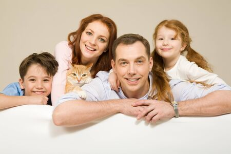 Happy couple and their two children smiling with pet among them Stock Photo - 4544923