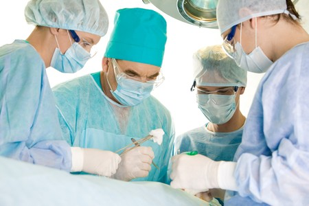 physicals: Several surgeons surrounding patient on operation table and looking at her during their work