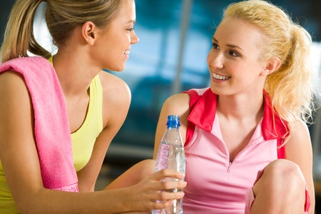Portrait of two pretty friends having a chat during workout in gym photo
