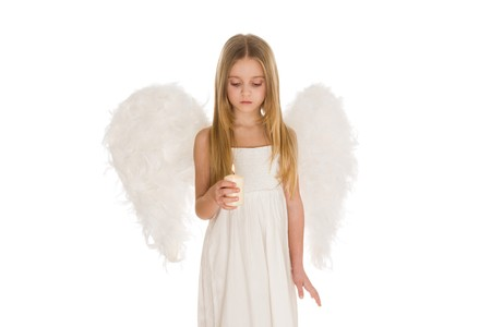 Image of cute girl with white wings behind looking at lit candle in hands photo