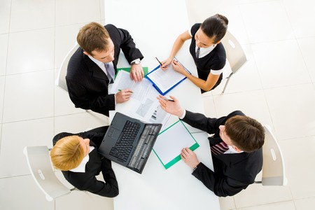 workteam: Above view of friendly workteam discussing business plans at meeting Stock Photo