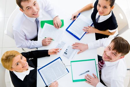 Several white collar workers looking upwards at camera from their workplace Stock Photo - 4549476