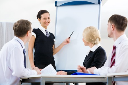 Photo of successful female standing by whiteboard while explaining her idea to colleagues Stock Photo - 4544840