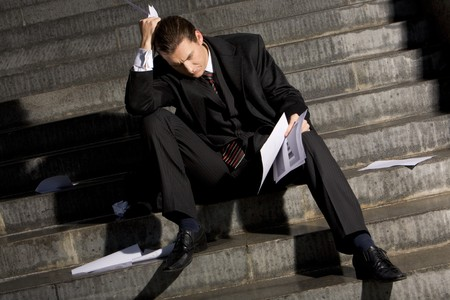 no idea: Photo of sad man with papers in hands sitting on stairs with no idea what to do